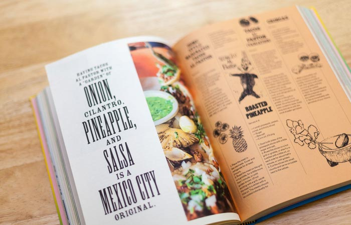 Tacopedia book, open, on a wooden table, two pages with text, illustrations and photos.