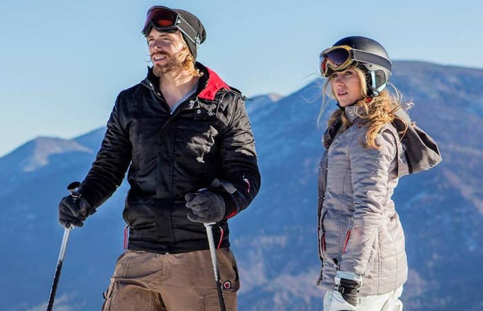A man and a woman in the mountain wearing ThermalTech - The First Solar Powered Smart Jackets.