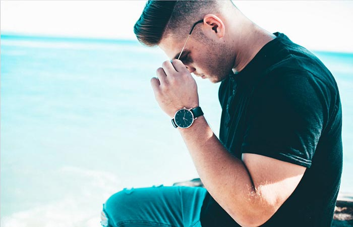 Thread Etiquette Classic – Rose Gold / Black Leather Timepiece on the hand of a man sitting on the shore in jeans and a black tee shirt.