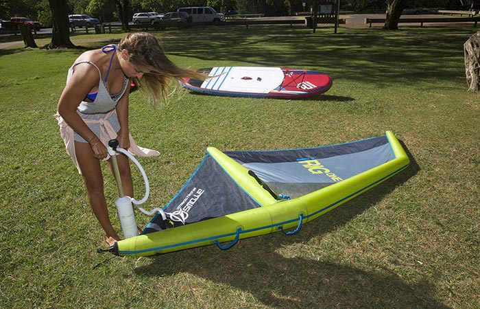 A woman inflating the iRig One with a pump, standing bent down on grass, with a board in the background.