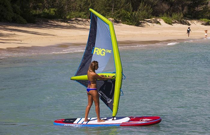 A woman windsurfing using the iRig One, back view, with a beach in the background.