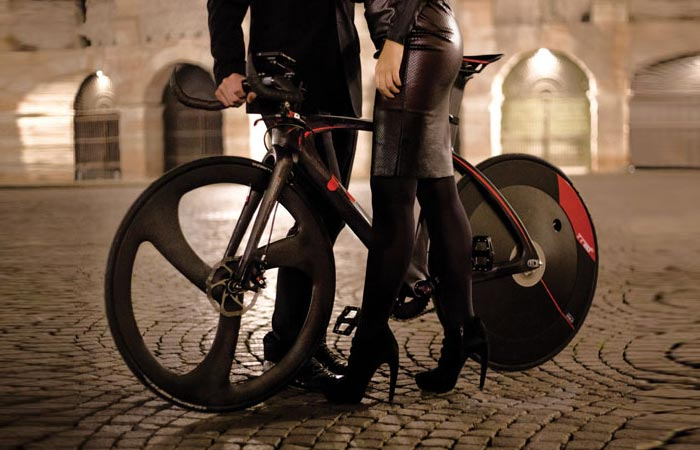 T°RED BestiaNera Hybrid Bike , on a city square, with lower bodies of a man and a woman on the opposite sides, tilted.