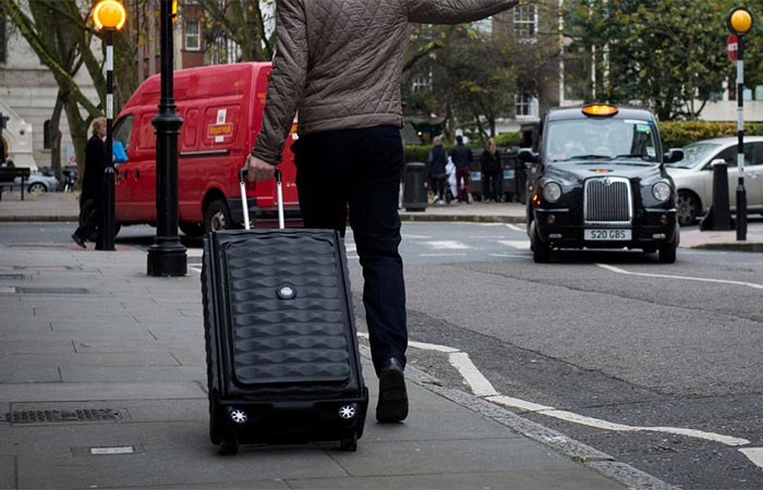 A Guy Carrying Néit Suitcase On The Street
