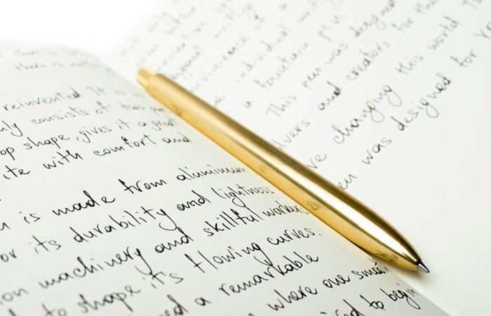 Gold SENS Pen On A Notebook With Writings On It
