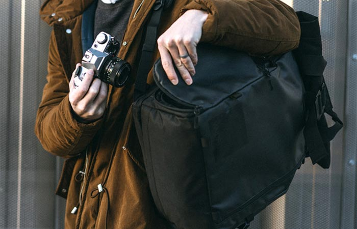 A Guy Placing A Camera Into PRVKE Travel and DSLR Camera Backpack