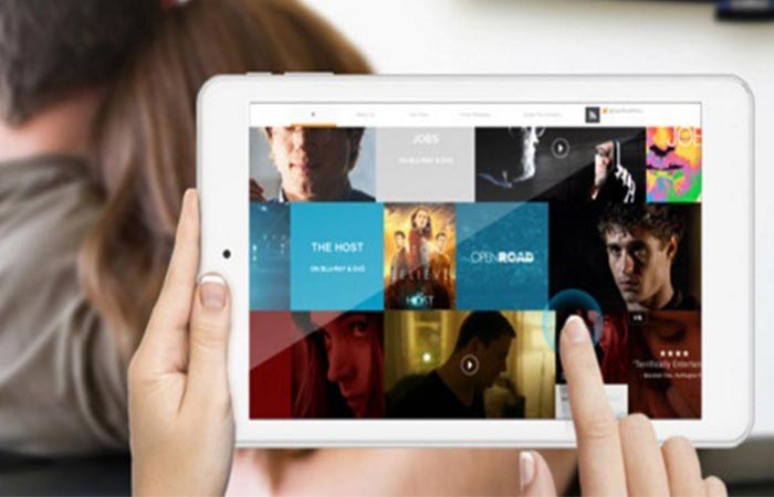 A woman selecting movies while streaming to the TV on the iWork8