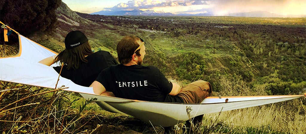 Two people looking over the landscape while relaxing in a Tentsile T-Mini Hammock