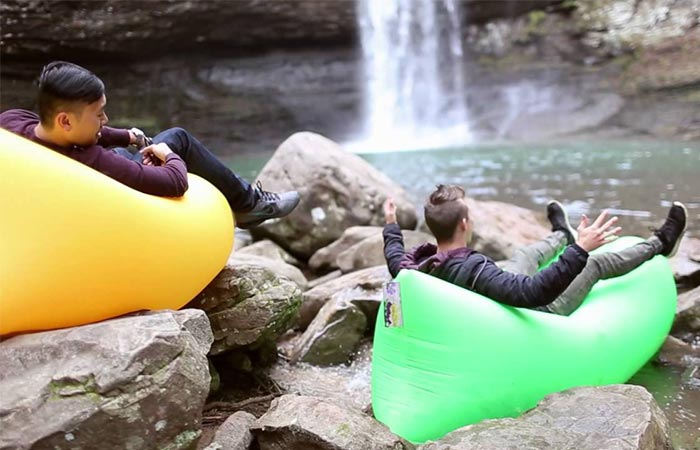 Two people sitting on green and yellow windpouches on rocks close to a waterfall