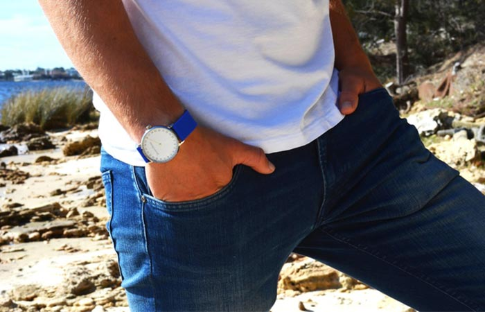 White Jacobo Dondi watch with blue strap on man's wrist.
