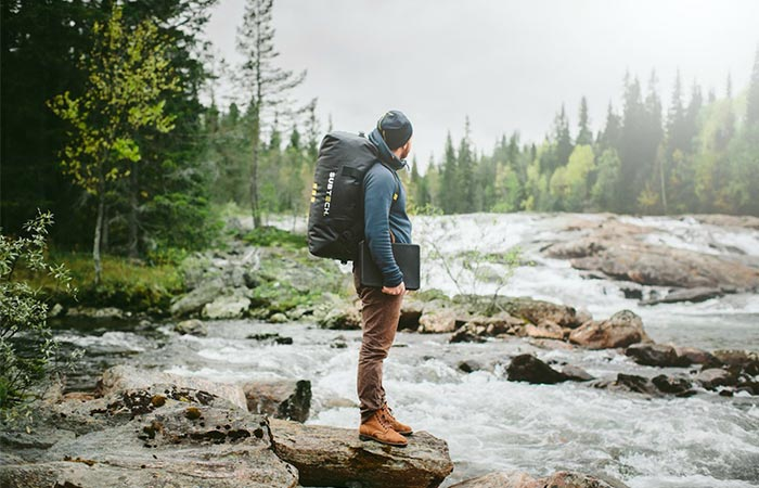 A Guy Standind On A Rock With Subtech Pro Drybag