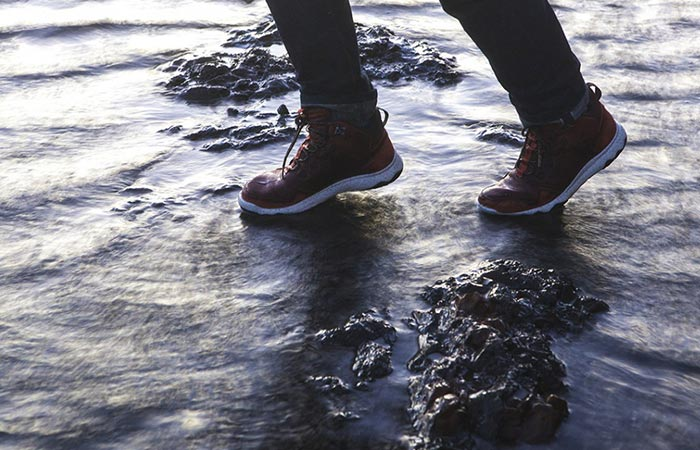 Man traversing water with a pair of Arrowood Luc Mid Hikers
