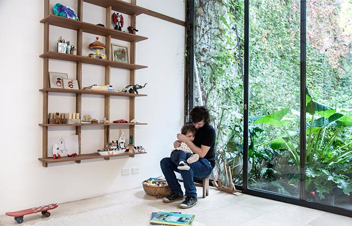 Man sitting with a child in front of Sticotti Bookshelf