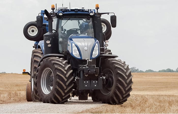 The New Holland T8 NH standing on a gravel path