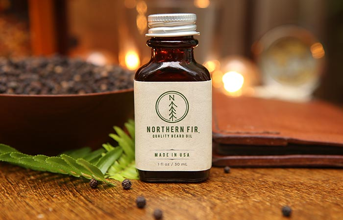 Shot of Norther Fir Beard Oil on a table with some pepper and cedarwood