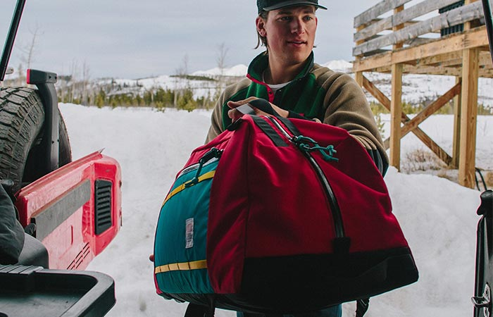 A Guy Putting Red Topo Designs Mountain Duffel In The Car