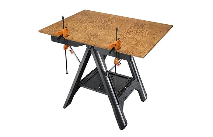 WORX Pegasus Folding Work Table in table mode with a piece of hard board on it