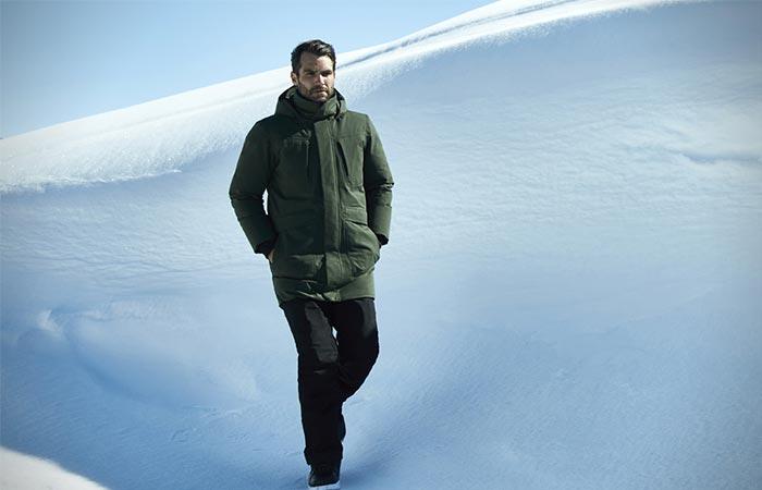 A Guy Walking Down A Snowy Hill Wearing A Green Jacket