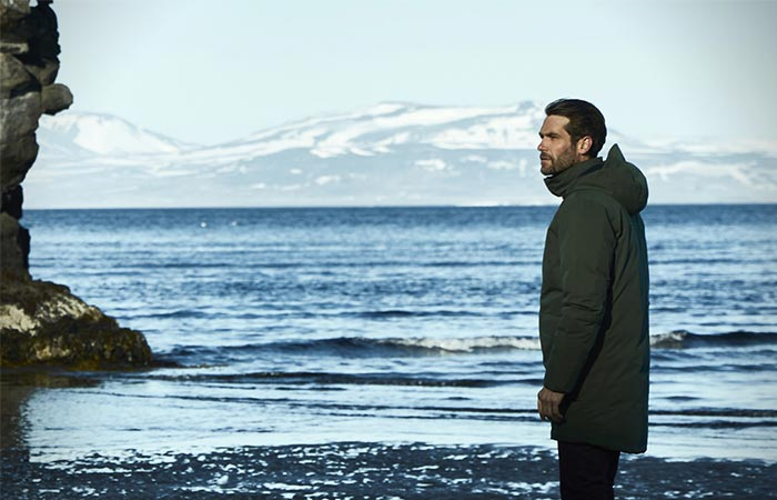 A Guy Standing Next To The Water In Aether Apparel's Tromso Jacket