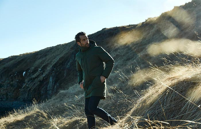 A Guy In Green Aether Apparel's Tromso Jacket Walking Down The Hill