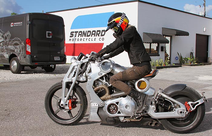 Somebody sitting on a bike wearing the Bell Moto 3