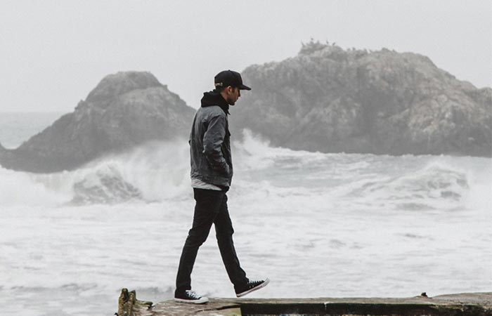 A Guy Walking Next To Water In Iron And Resin X Huckberry Rambler Jacket