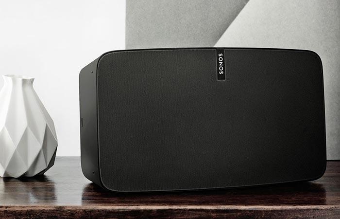 Black Sonos Play 5 on a wooden shelf