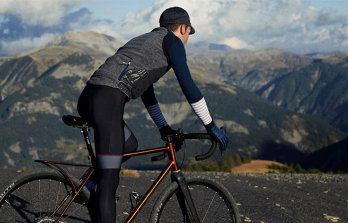 a guy on a bike wearing a grey and blue cycling vest