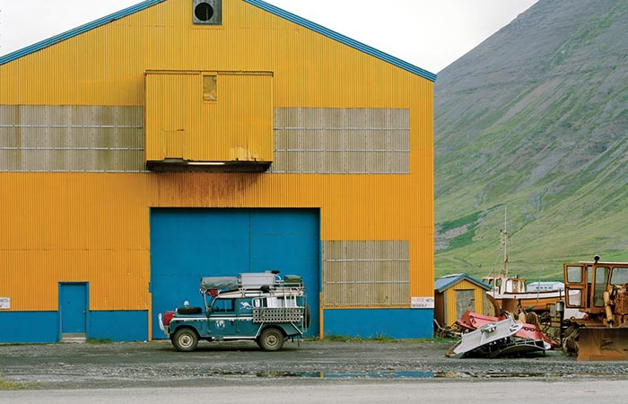 Alloy + Grit Magazine Photo of a Land Rover in front of a blue and yellow shed
