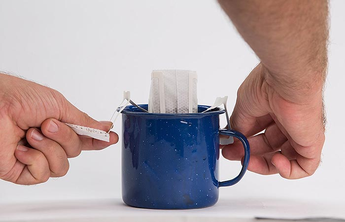 Man attaching Libra Pourtable coffee bag to the sides of the mug