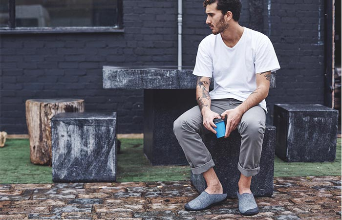 A guy sitting outside wearing wool slippers