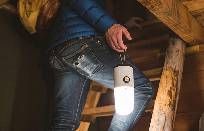 a guy carrying a portable camping LED lantern