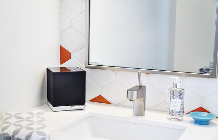 a black cube speaker in the bathroom