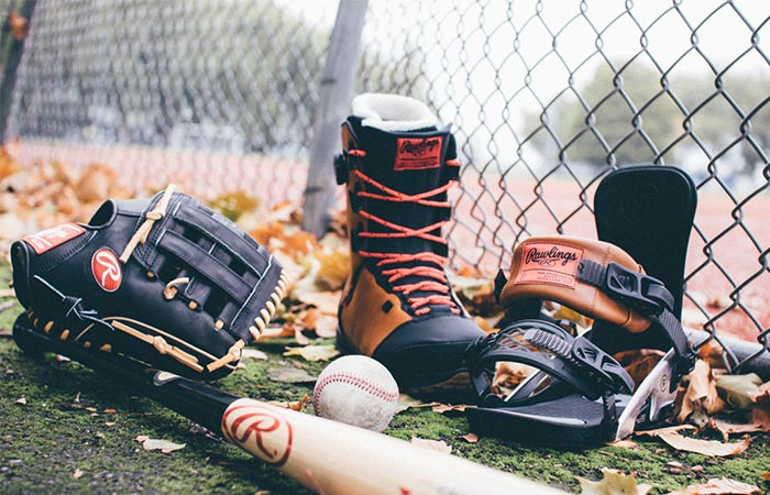 Fuse By Ride boot next to harness, baseball, baseball bat and mitt.
