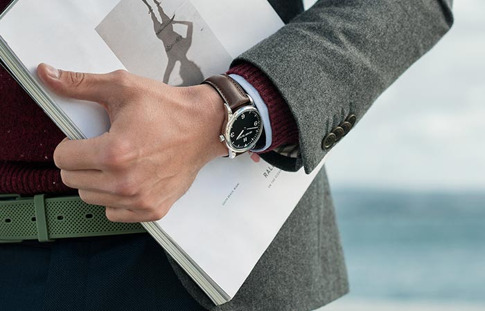 Man wearing a Henry Blake watch while carrying papers