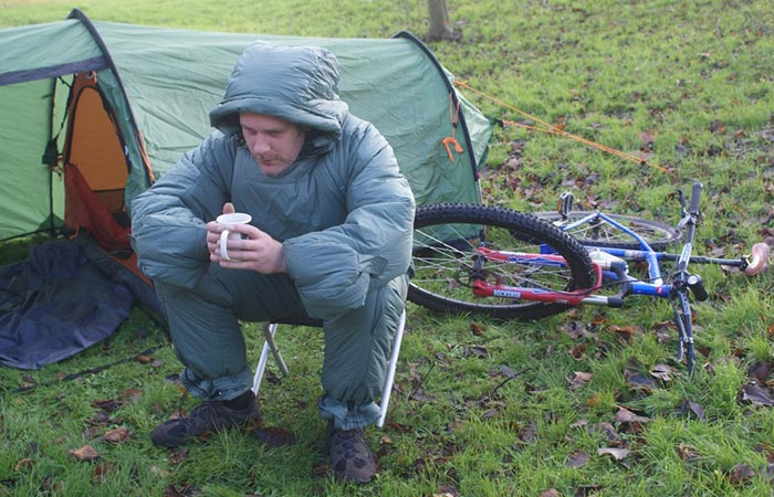 Selk'bag Patagon Duck Green being worn by a man drinking coffee next to a tent