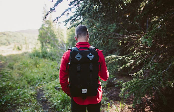 Man wearing the Topo Designs X Woolrich Klettersack Olive Waffle in the forest