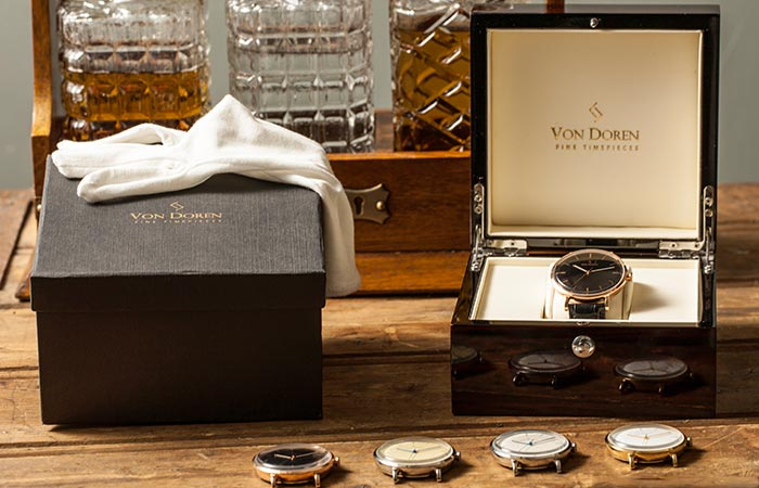 Von Doren watch faces on table and the box that it comes with