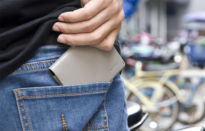 Man placing the grey Ikepod wallet into his pocket