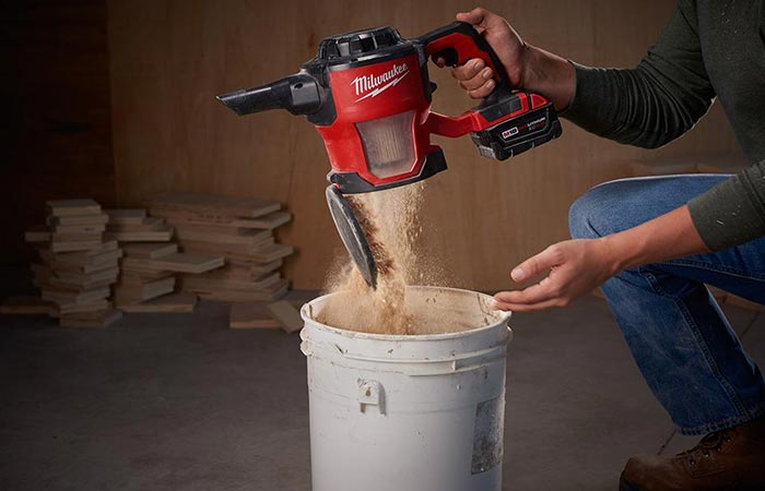 Milwaukee M18 Compact Cordless Vacuum Cleaner being emptied by a man in a workshop