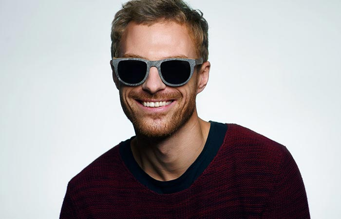 a guy wearing wooden glasses with a stone finish