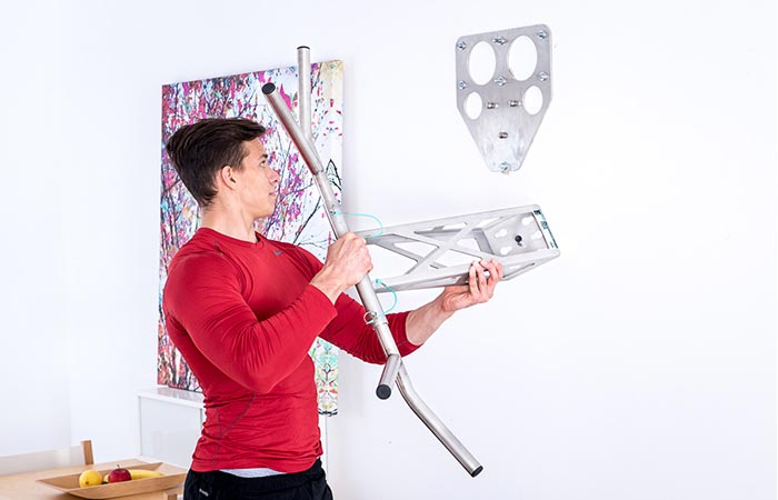 Man placing the Pullup & Dip on its indoor bracket