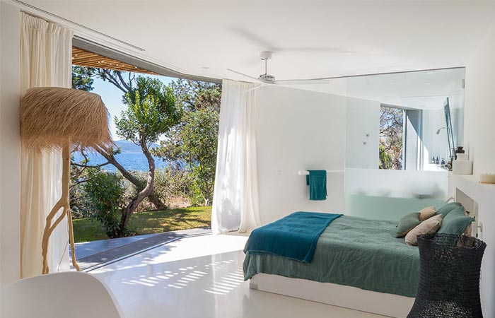 a bedroom with an open view of the sea
