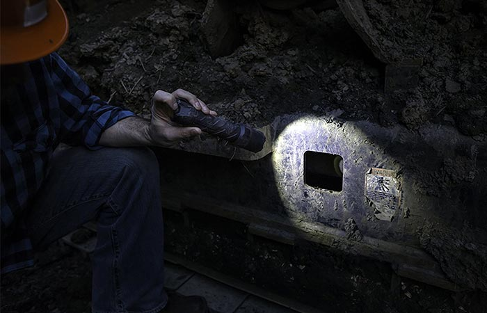 Man using the Coast Polysteel to look into a hole