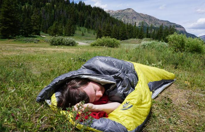 Man using the Sierra Designs Backcountry Elite Sleeping Bag in a mountainous area.