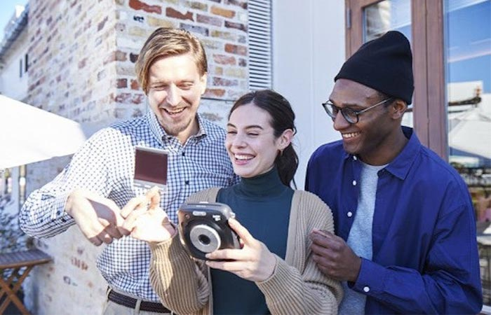 three people using an instant camera