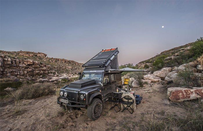 a land rover with a rooftop sleeping addition