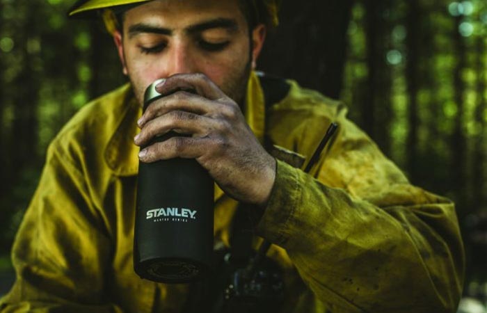 a guy drinking from black stanley vaccum bottle