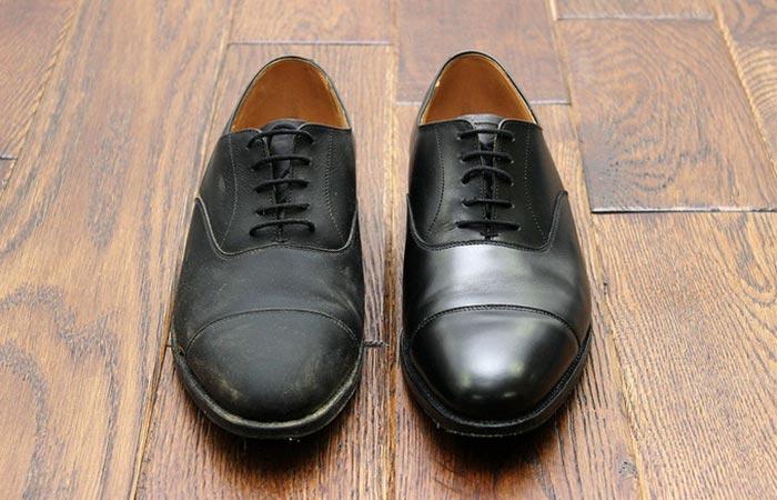 one unpolished and one polished black leather shoe