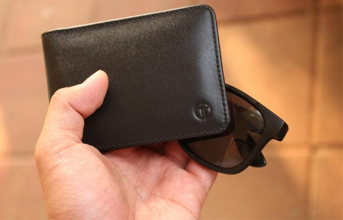 holding sunglasses and Slim Bifold Wallet