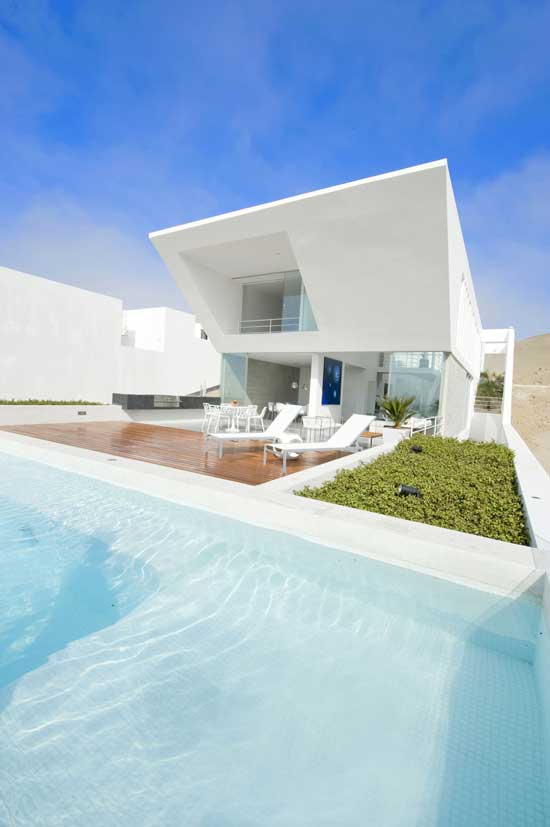 exterior view of a home with white facade and pool on a sunny day